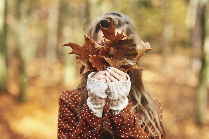 Young woman with autumnal leafs