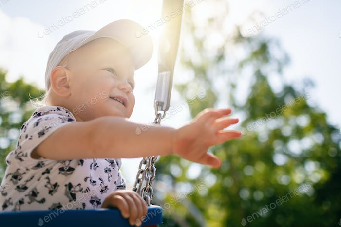 Baby boy playing in playground having fun