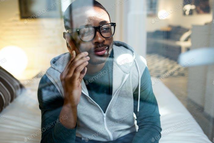 Hermoso joven negro usando su teléfono móvil en casa.