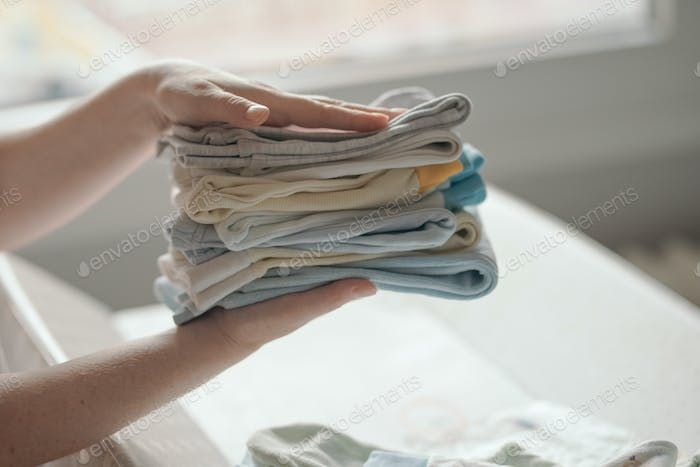 Mother sorting newborn baby clothing at home