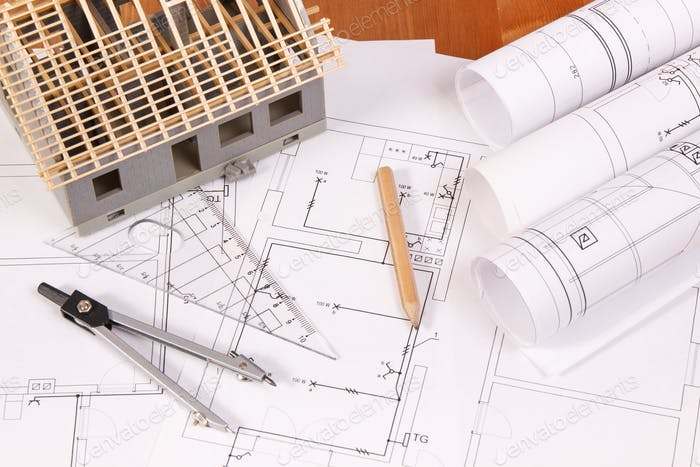 Electrical diagrams, accessories for engineer jobs and house under construction on desk
