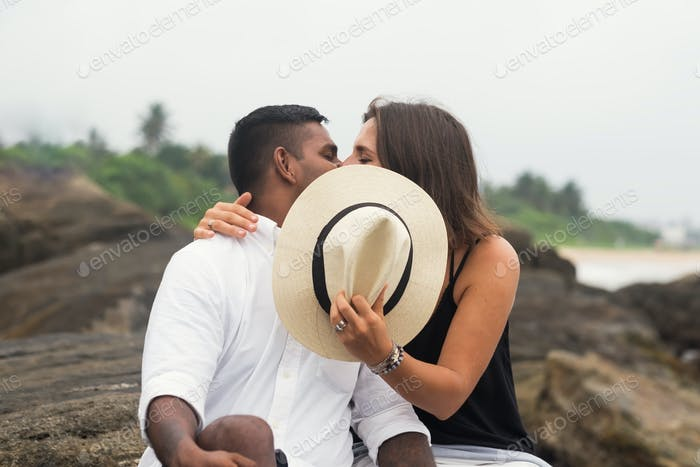Young mixed race couple kissing sitting on stone. They close faces with hat.