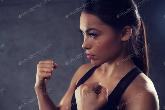 woman holding fists and fighting in gym