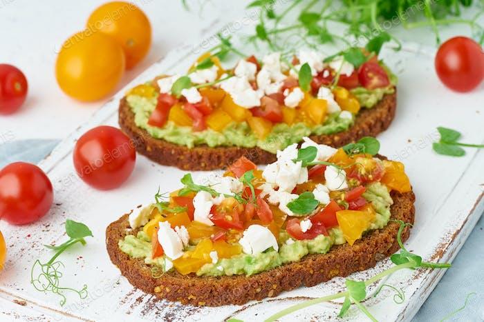 avocado toast with feta and tomatoes, smorrebrod with ricotta, closeup
