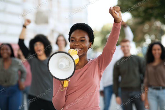Female leader of strikers with loudspeaker yelling demands to government