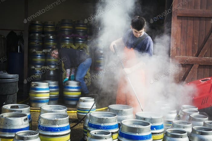 Man working in a brewery, cleaning metal beer kegs with a high pressure washer.