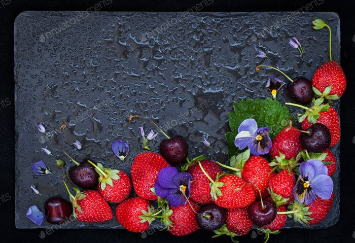 Fresh summer ripe strawberry and cherry on dark background, top