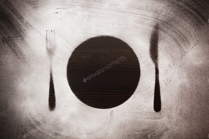 silhouette plate, fork and knife on black background wooden surface sprinkled powder