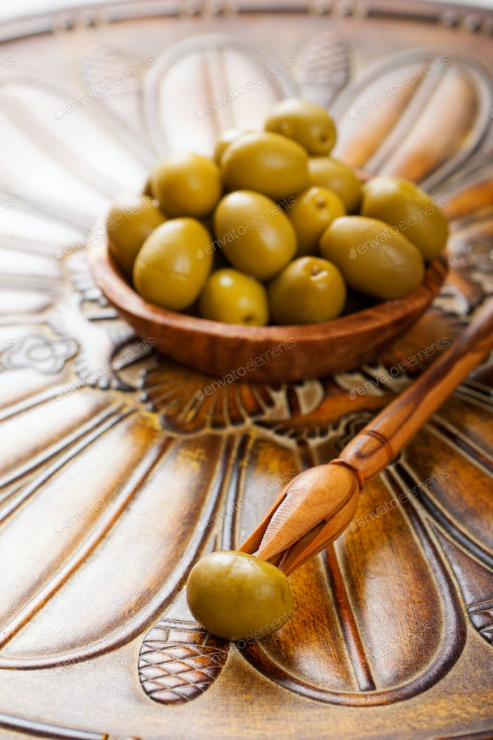 Stick with olive and bowl with green olives