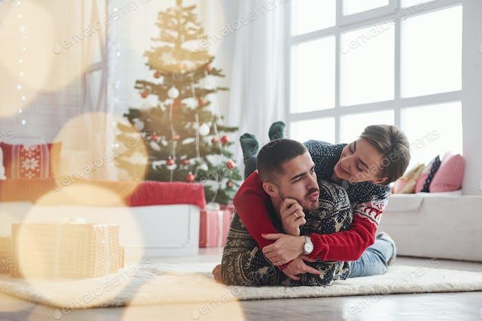Hermosa pareja joven acostada en la sala de estar con árbol de vacaciones verde en el fondo