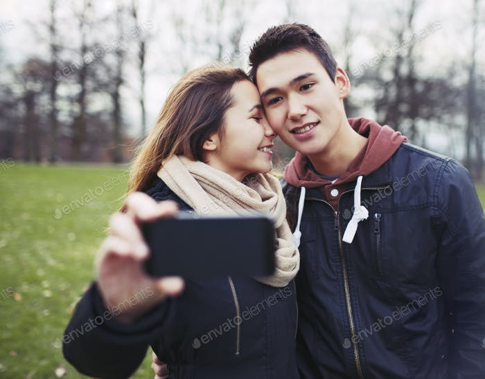 Affectionate young couple taking pictures using a smart phone