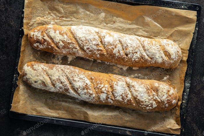 Two fresh whole grain bread baguettes.