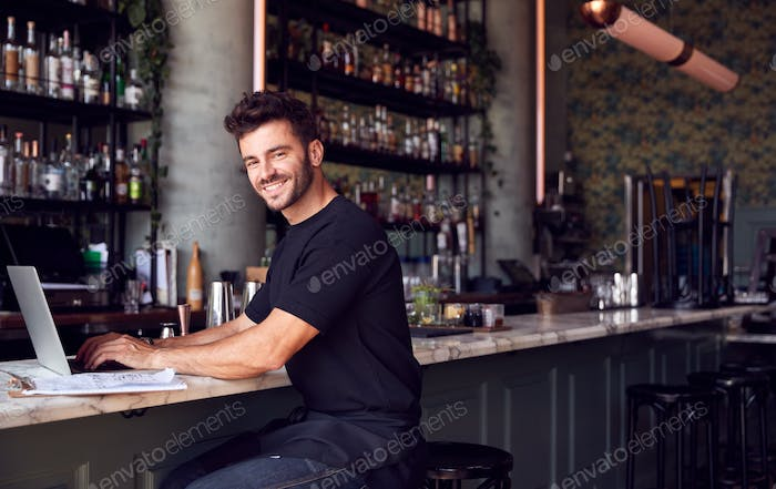 Portrait Of Male Owner Of Restaurant Bar Sitting At Counter Working On Laptop