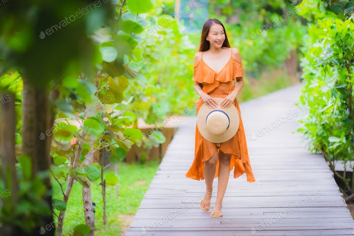 Portrait beautiful young asian woman walk on path walk in the ga