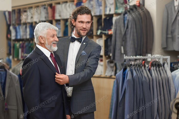 Attractive helping customer trying on jacket in show room