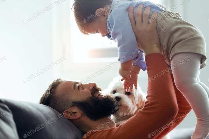 Handsome young father playing with his baby while the dog looking them on sofa at home.