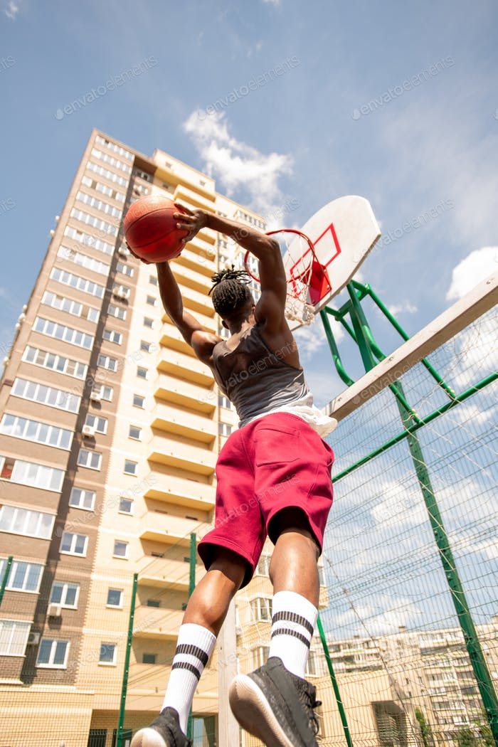 African basketball player jumping while going to throw ball in basket