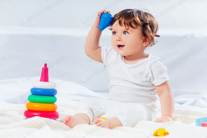 Happy baby boy sitting with toy