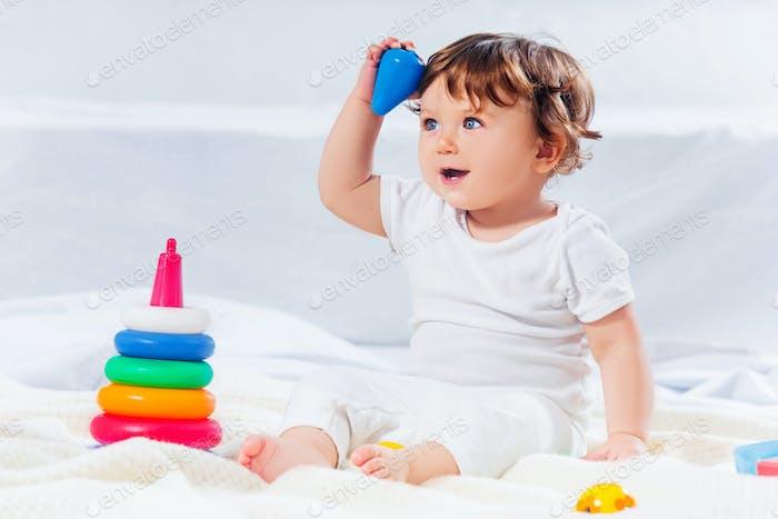 Glücklicher Baby Junge sitzend mit Spielzeug