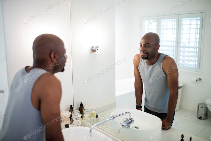 Man looking at himself in bathroom mirror