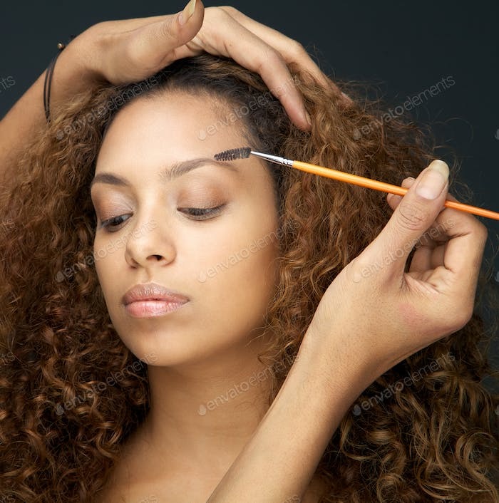 Beautiful woman having eye make up application from professional