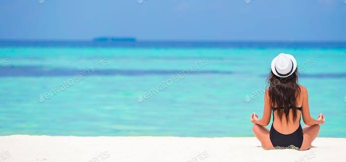 Junge Frau sitzt in Yoga-Position während des tropischen Urlaubs
