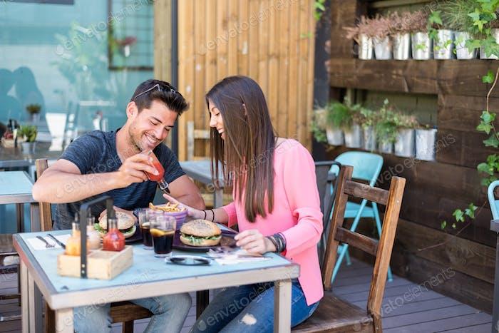 Glückliches junges Paar Sitzgelegenheiten in einem Restaurant Terrasse Essen eine Burg