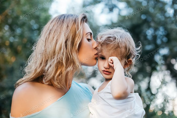 mother kissing crying daughter outdoors