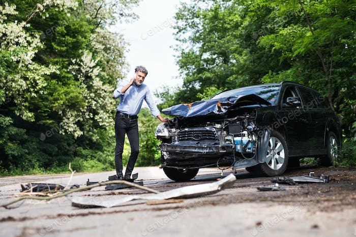 Mature man standing by the car, making a phone call after a car accident.