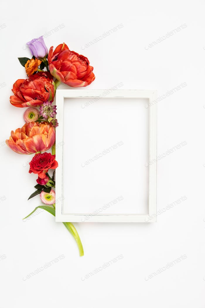 White vintage frame and flowers on a white background