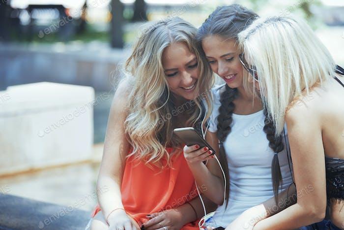 Three female friends with smartphone having fun in social media