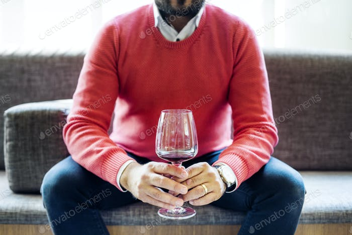 Midsection of man holding red wineglass while sitting at Lebanese restaurant