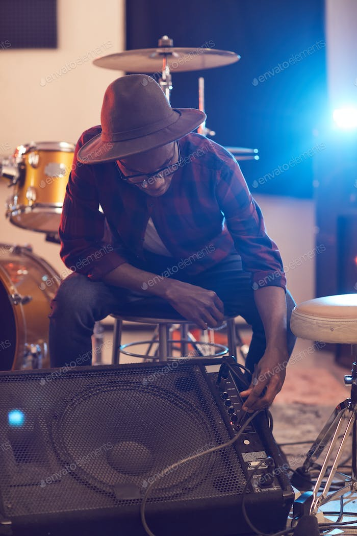 African Young Man Setting Up Amplifier