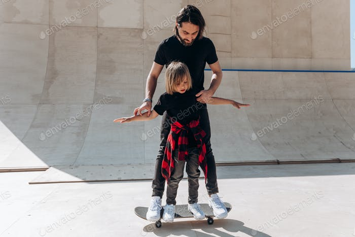 Young father helps his little son to ride on the skateboard in a skate park at the sunny day