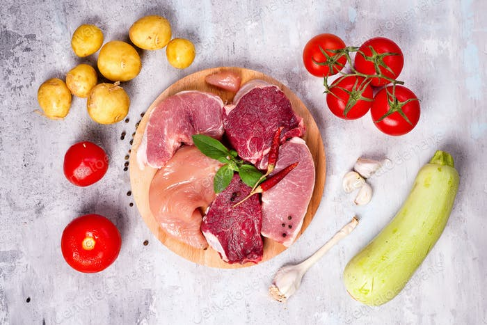 Selection of different raw meat with vegetables at wooden board .Lean proteins.