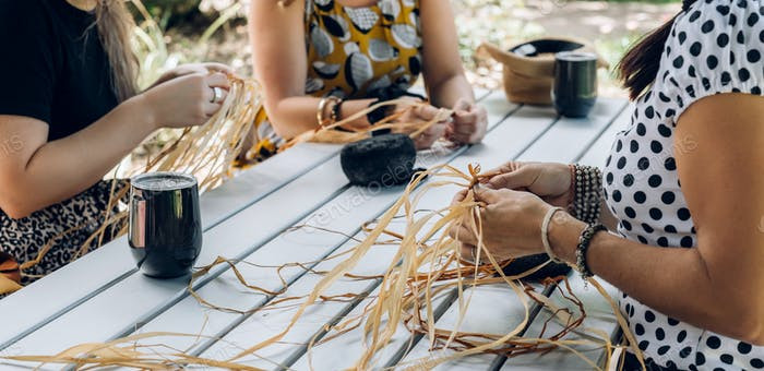 Females weaving baskets on the craft workshop. Hands holding the craftwork, close up shot