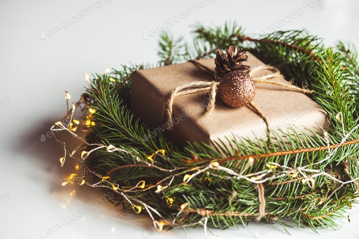 Gift in craft paper in a wreath of Christmas trees. Christmas mood, New Year, On white background