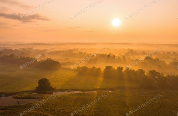 Naturlandschaft mit Sonnenaufgang über Land mit Nebel bedeckt