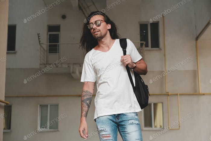 Man on urban background with backpack and sunglasses