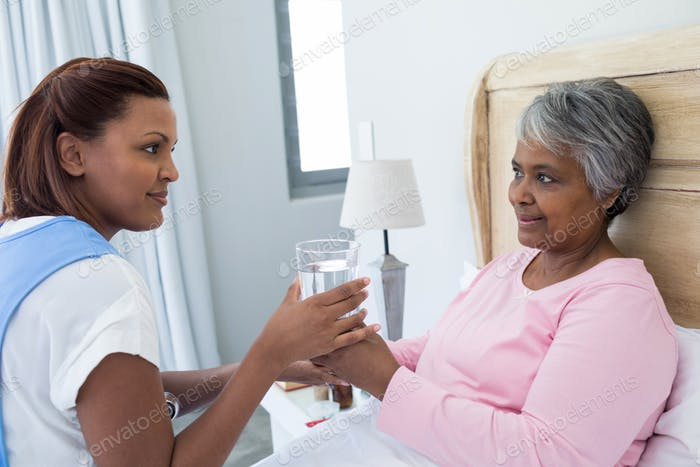 Female doctor giving glass of water to sick senior woman on bed