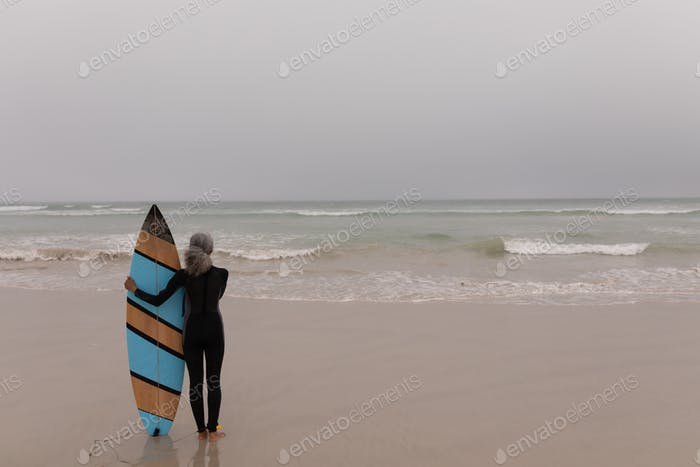 Rear view of senior female surfer with surfboard standing on the beach