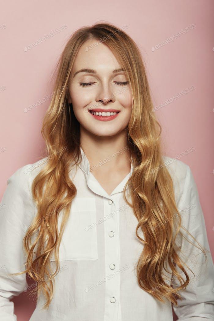 Ziemlich junge Frau posiert auf rosa Hintergrund