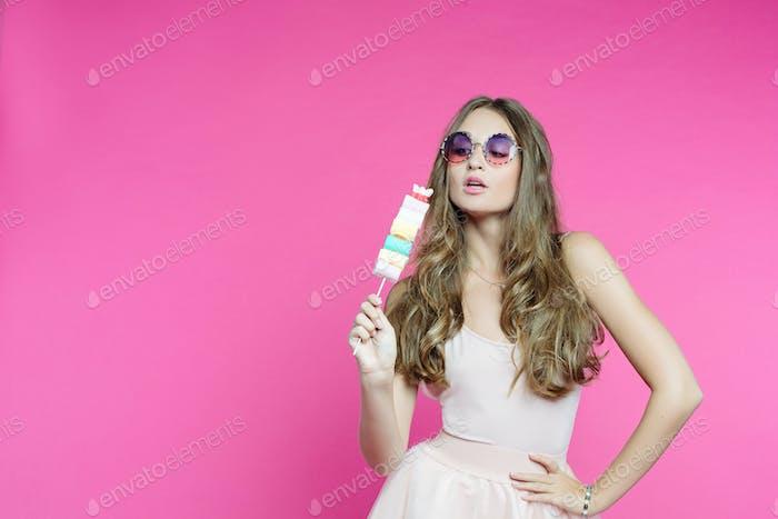Verführerische Frau wie süße Puppe mit Marshmallow-Bonbons