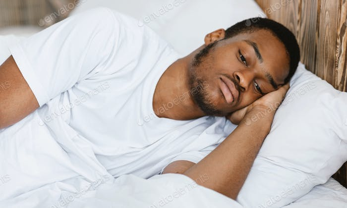 Depressed African American Guy Lying Awake In Bed At Home