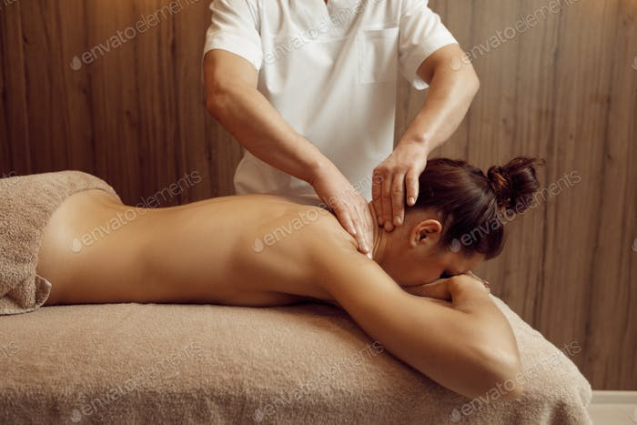 Male masseur hands pampering neck to young woman