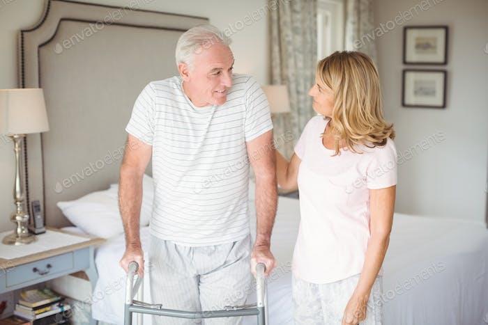 Mujer mayor ayudando Hombre a caminar con walker