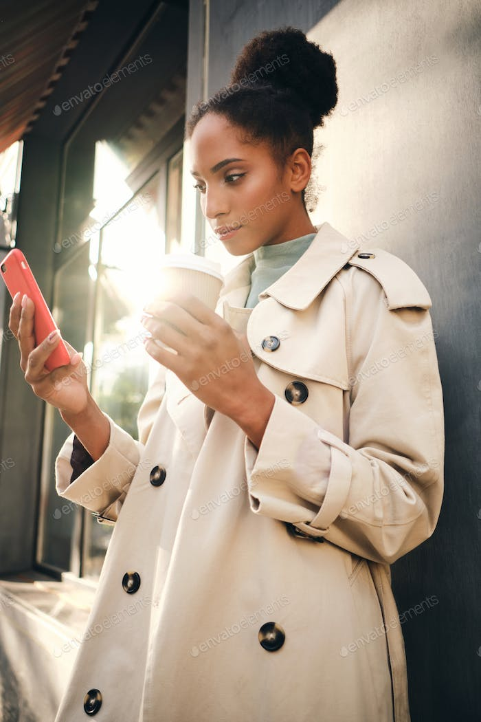 Serious African American girl in stylish trench coat with coffee confidently using cellphone outdoor