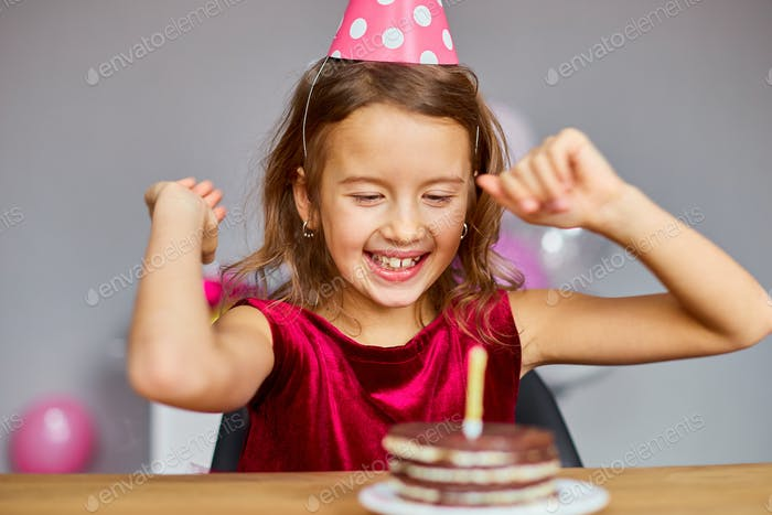 A smile and happy little girl is wearing a birthday hat looking at a Birthday Cake, blowed candles