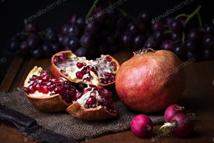 Granatäpfel und Trauben mit anderen Früchten Bodegon mit klassischem Licht auf Holz