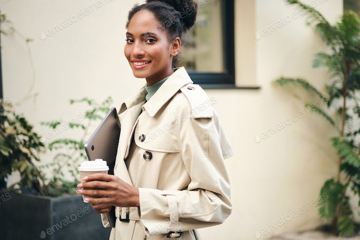Attractive African American student girl in trench coat with laptop happily looking in camera